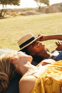 Smiling women lying in a park
