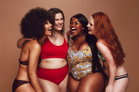 Different size females in bikinis laughing together