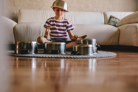 Little musician playing drums on kitchenware