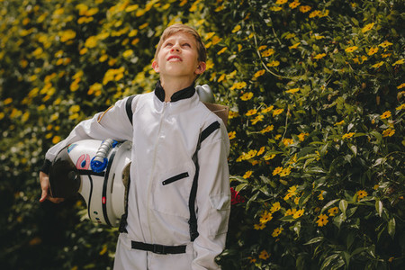 Boy astronaut standing outdoors and looking up