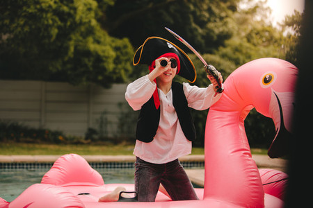 Kid playing pirate on inflatable mattress in pool