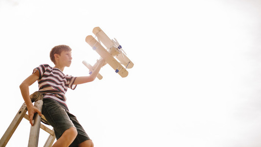Boy on top of a ladder with toy airplane