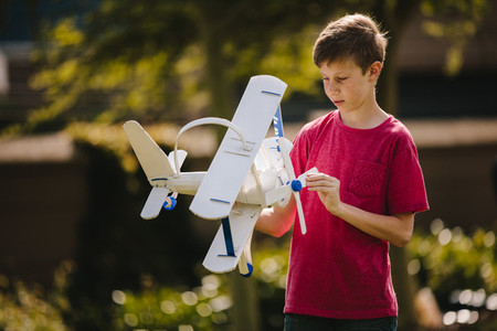Boy playing with a toy plane outdoors
