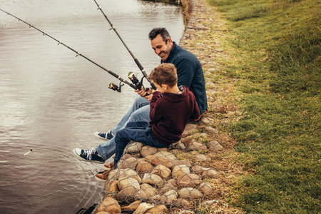 Father and son enjoying fishing sitting near the lake