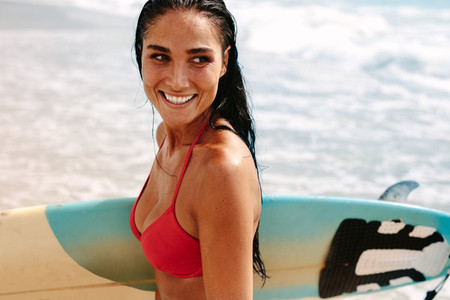 Female surfer at the beach with her surfboard
