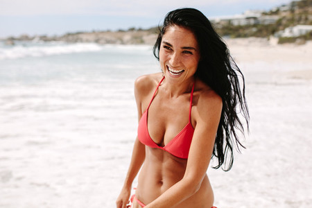 Cheerful woman in bikini running on the beach
