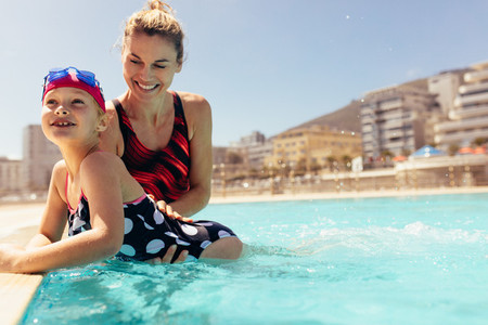 Happy female teaching a girl to swim