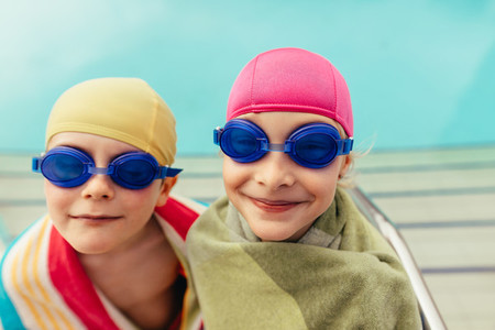 Two kids wrapped in towel by poolside
