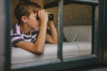 Boy looking outside window using binoculars