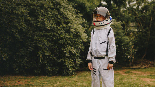 Cute boy playing astronaut in playground