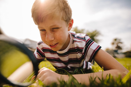 Boy exploring nature with magnifying glass