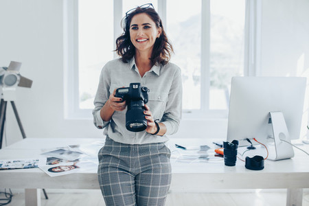Photographer with a professional camera in office