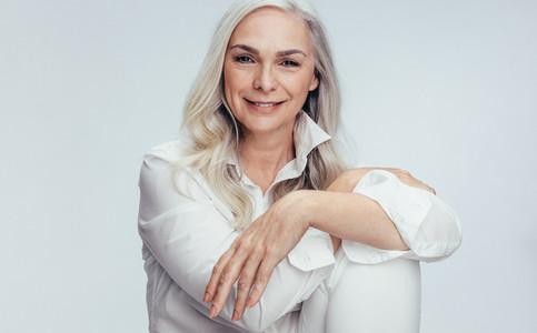 Beautiful mature woman sitting over white background