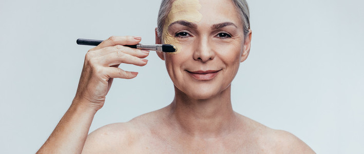 Senior woman applying liquid foundation