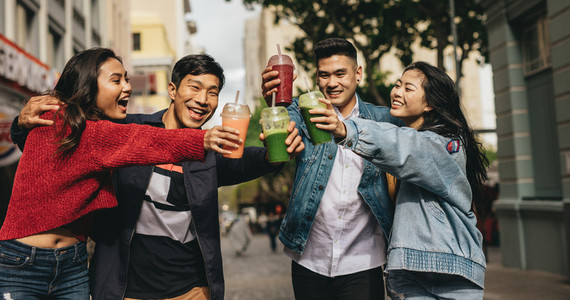 Cheerful friends toasting drinks on the street