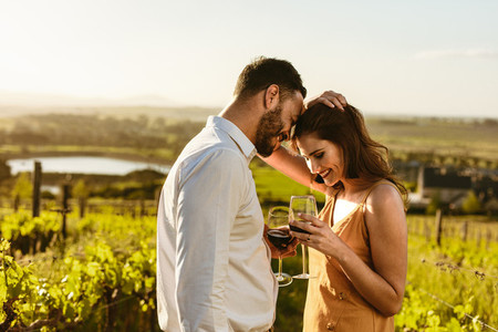 Couple in love standing in a vineyard holding wine