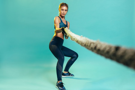Strong athlete working out with battling rope