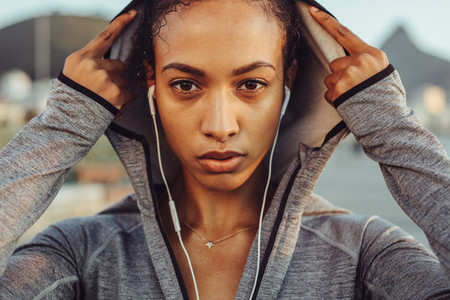 Confident female runner in a hoodie