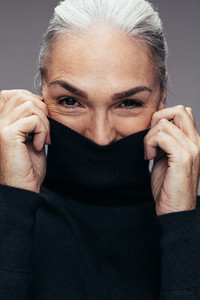 Mature woman covering her face with top