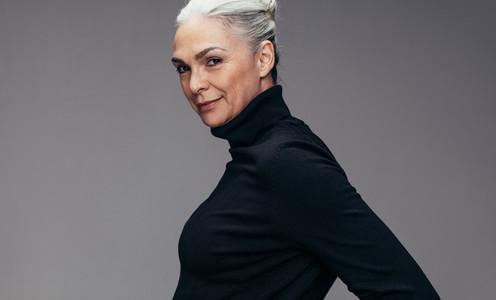 Confident senior lady on grey background