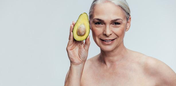 Elderly woman showing an avocado