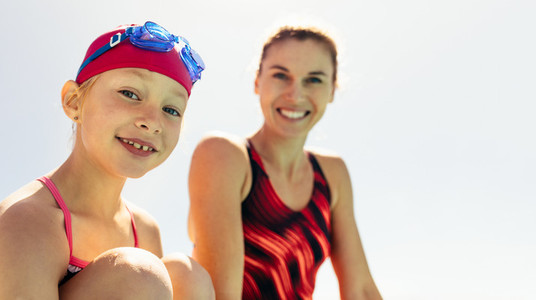 Smiling girl with swimming trainer