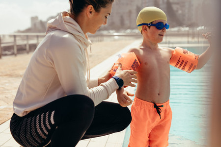 Boy at swimming class with trainer