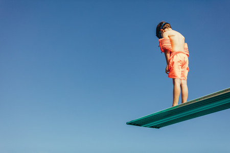 Boy learning on diving spring board