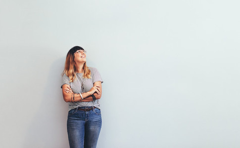 Woman standing against wall looking away