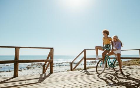 Joyful friends riding a bicycle