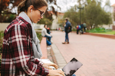 Female college student using laptop at campus