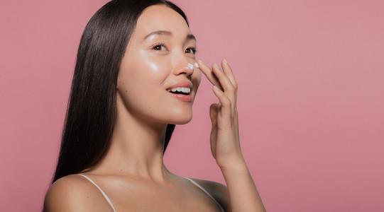 Youthful female model applying moisturizer