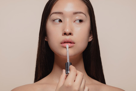 Woman applying transparent lip gloss