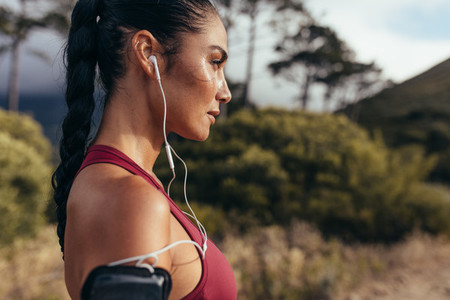 Woman athlete with earphones outdoors