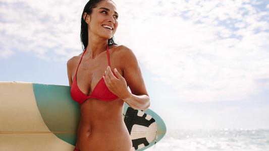 Beautiful female surfer in the beach