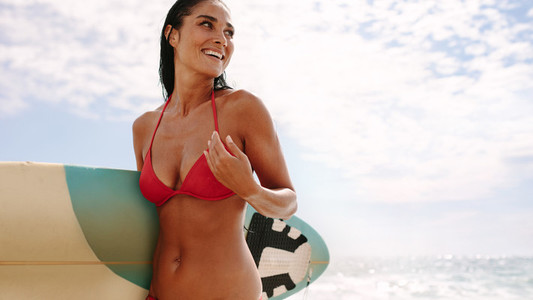 Beautiful female surfer in the beach