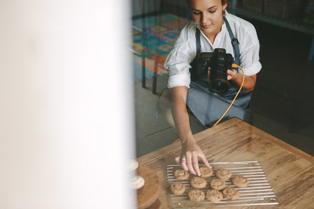 Woman chef photographing pastries