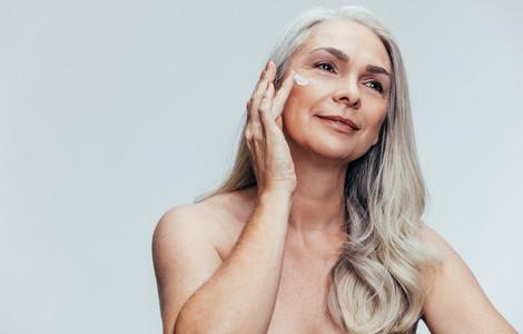 Senior woman putting on anti aging cream