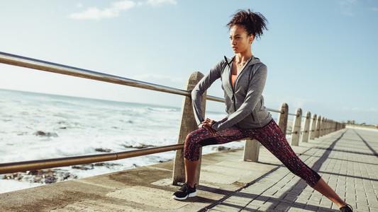 Woman stretching at seaside promenade