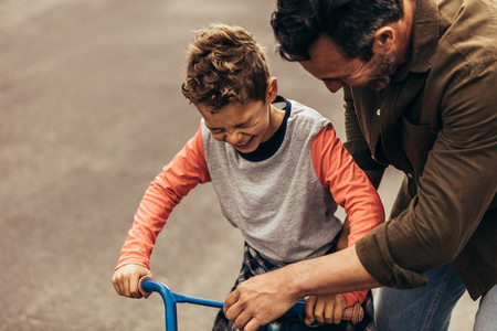 Kid having fun learning to ride bicycle