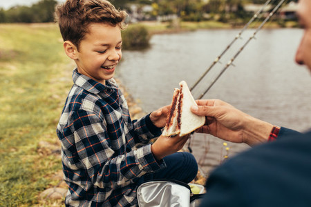 Father and son on a day out fishing near a lake