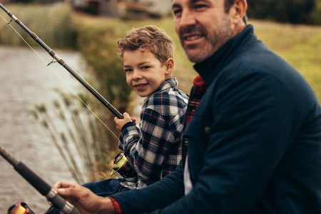 Close up of father and son fishing near a lake