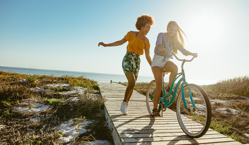 Friends enjoying themselves with a bicycle