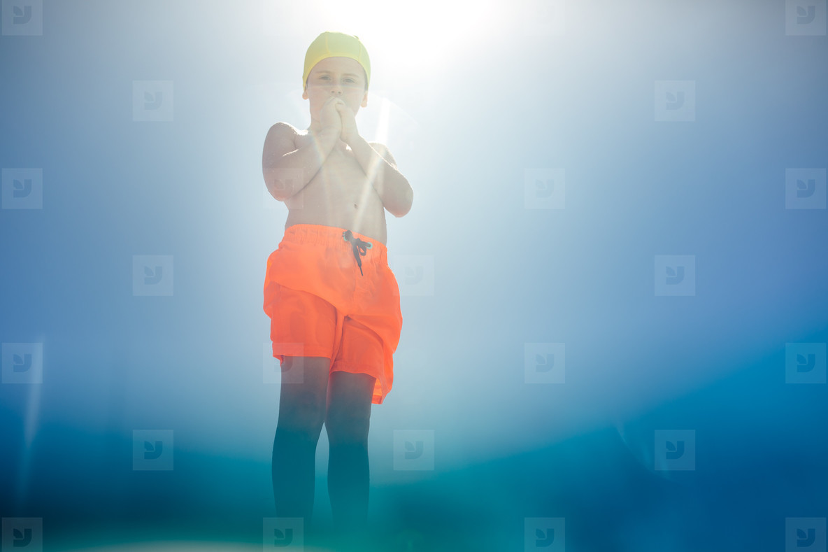 Boy in swimming costume at outdoor pool