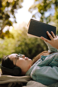 Relaxed woman reading a book outdoors