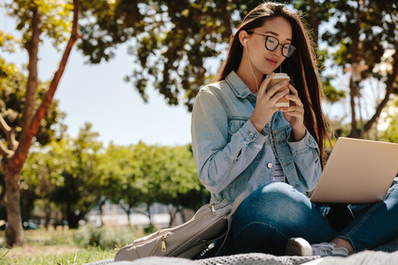 College girl sitting in campus using a laptop