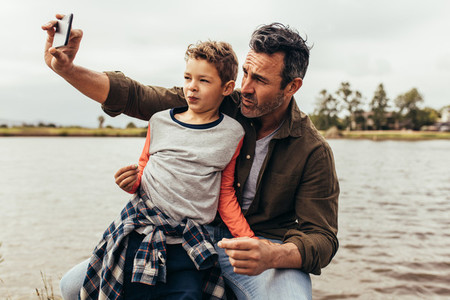 Father and son clicking a selfie near a lake