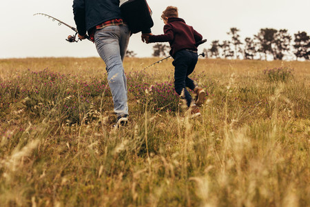 Father and son going for fishing holding fishing rods
