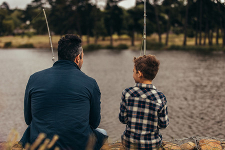 Father and son spending time together fishing in a lake