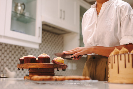 Confectioner cuts a homemade cupcake